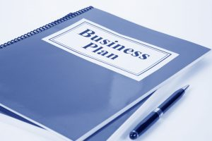 """Document with a blue cover labeled """"Business Plan"""""""